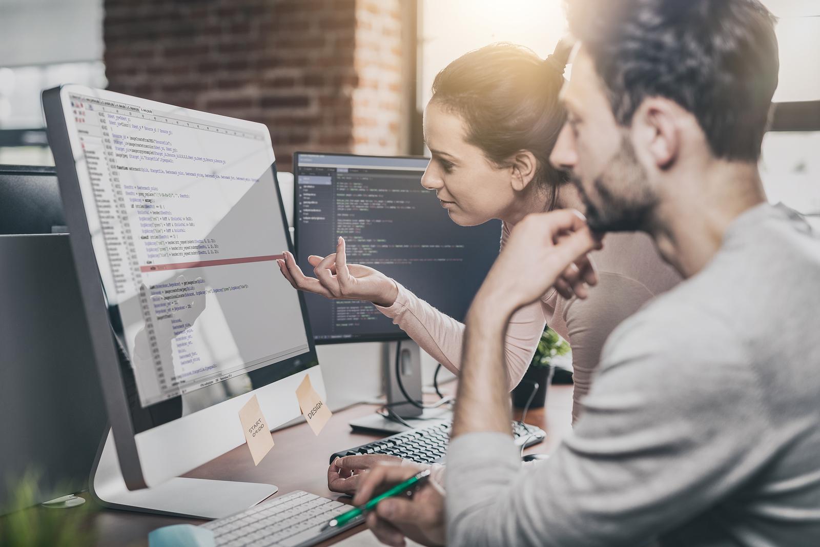 Dois programadores desenvolvendo e examinando códigos de programação.